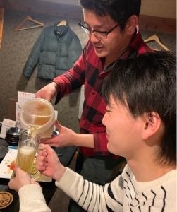 六崎弟にビールをつぐ木本